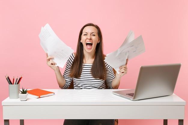 Jonge gekke vrouw die schreeuwt en de hand spreidt met papieren documenten die aan een project werken terwijl ze op kantoor zit met een laptop