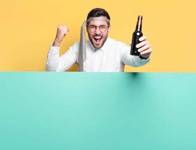 Jonge gekke zakenman met een bierfles die goed nieuws viert