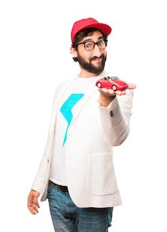 Jonge gekke zakenman met een rode auto speelgoed