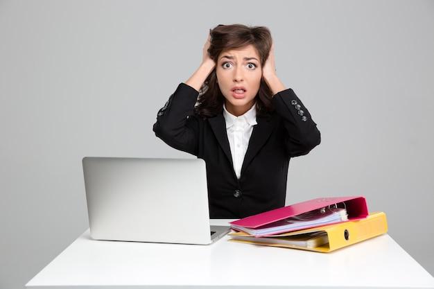 Jonge gekrulde behoorlijk geschokte gestresste zakenvrouw die haar hand tegen het hoofd houdt en met laptop en documenten werkt