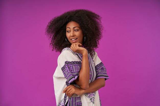 Jonge, gekrulde, donkere vrouw, gekleed in een wit overhemd met een patroon aanraken van gezicht met opgeheven hand, terugdraaien en kijken op de schouder met een vrolijke glimlach, poseren op paars