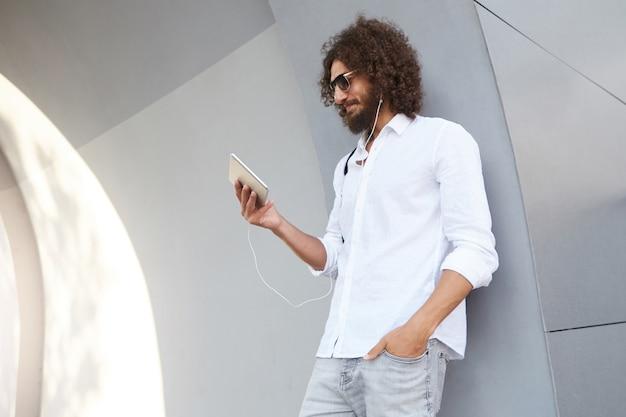 Jonge gekrulde donkerharige man met baard, leunend op grijze muur, videobellen en praten met iemand met behulp van een koptelefoon
