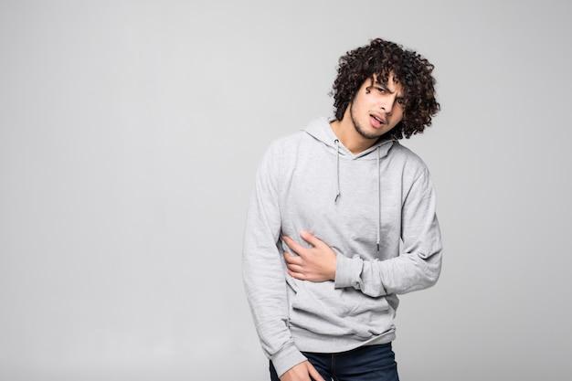 Jonge gekrulde knappe mens die aan pijn wegens sedentaire levensstijl lijden die op witte muur wordt geïsoleerd