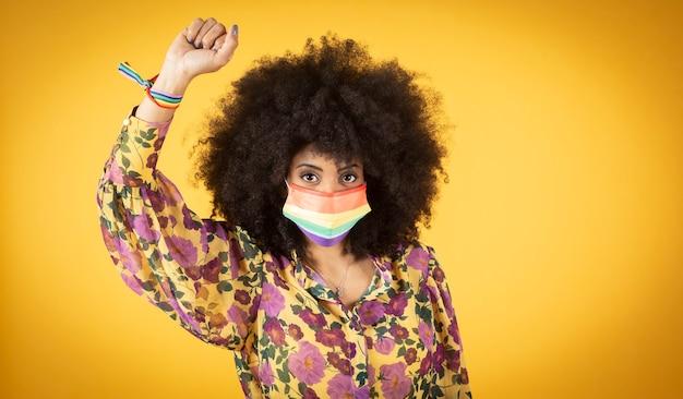 Jonge gekrulde lgbt-vrouw. enkel en alleen. mooie gelukkige jonge afrovrouw met symbool van lgbt
