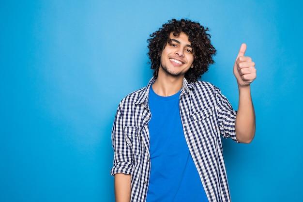 Jonge gekrulde mens met duimen die omhoog op blauwe muur wordt geïsoleerd