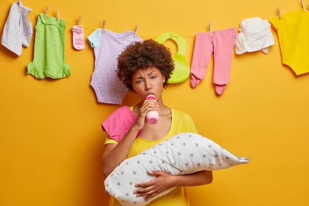 Jonge gekrulde moeder is moe van het zorgen voor pasgeboren, houdt baby gewikkeld in een deken, zuigt melk uit de fles, voelt liefde voor dochtertje, bezig met huishoudelijke taken en borstvoeding