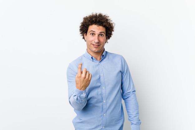 Jonge, gekrulde volwassen man die een elegant shirt draagt en met de vinger naar je wijst alsof ze dichterbij komen.