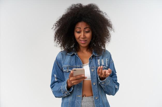 Jonge gekrulde vrouw met donkere huid die mobiele telefoon in de hand houdt en verwonderd naar het scherm kijkt, met witte top en jeansjas, poserend over witte muur