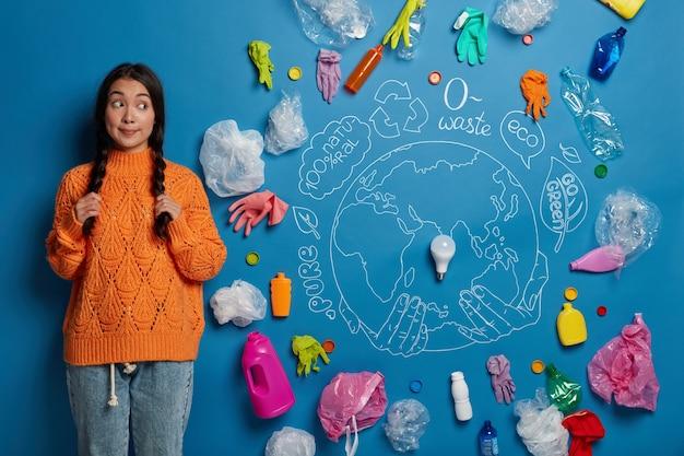 Jonge gekrulde vrouwelijke activiste houdt twee vlechten vast, kijkt opzij, demonstreert het probleem van plasticvervuiling met symbolische afbeelding