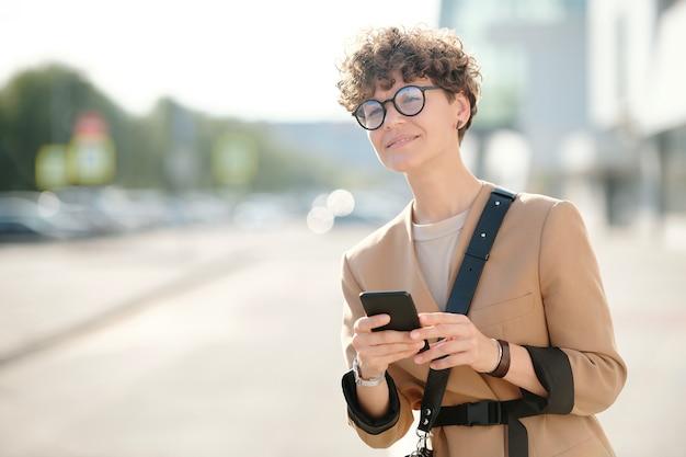Jonge gekrulde zakenvrouw met smartphone die over de weg staat, scrollt in smartphone en op zoek is naar een taxi tegen de stedelijke omgeving