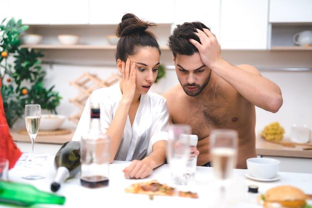 Jonge geliefden kijken naar foto's na een gek seksfeestje
