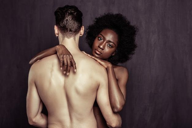 Jonge geliefden. leuke jonge vrouw aanraken van de schouders van haar vriendjes terwijl hem knuffelen