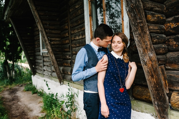 Jonge geliefden paar staande in de buurt van een oud houten stijlvol huis