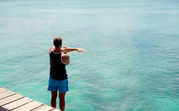 Jonge gelooide atleet die rekoefeningen op een oceaandok doet.