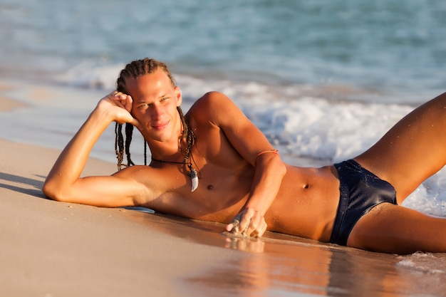 Jonge gelooide man met modern kapsel liggend op zand aan de rand van het zeewater en genieten van de zon op zonnige zomerdag. vakanties, reizen, actief gezond levensstijlconcept