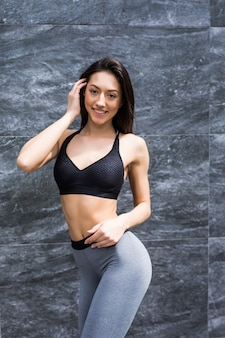 Jonge gelooide vrouw die sportieve kleren grijze bovenkant draagt die zich tegen muur bevinden.