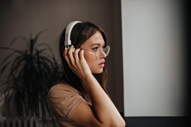 Jonge gelooide vrouw in witte hoofdtelefoons en glazen met serieuze blik vormt in de kamer.