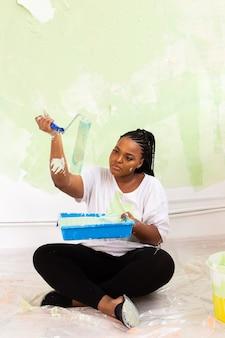 Jonge gelukkig afrikaanse amerikaanse vrouw schilderen binnenmuur met verfroller in nieuw huis. een vrouw