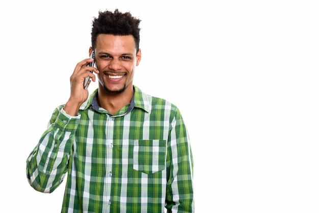 Jonge gelukkig afrikaanse man die lacht tijdens het gesprek op de mobiele telefoon