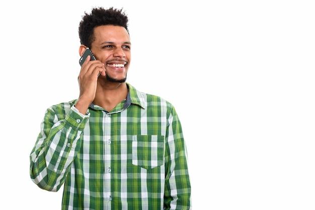 Jonge gelukkig afrikaanse man glimlachend tijdens het praten op de mobiele telefoon en denken