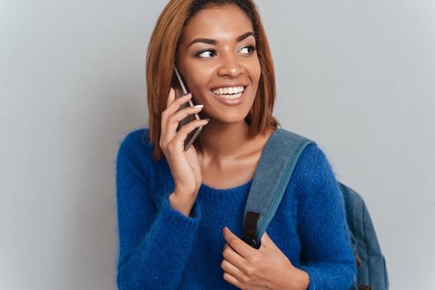 Jonge gelukkig afrikaanse vrouw in trui met rugzak praten aan de telefoon en opzij kijken.