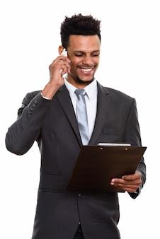 Jonge gelukkig afrikaanse zakenman glimlachen tijdens het lezen op klembord en praten over de mobiele telefoon
