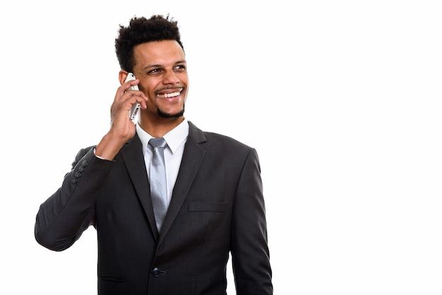 Jonge gelukkig afrikaanse zakenman lachend tijdens het praten op de mobiele telefoon en denken