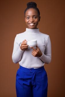 Jonge gelukkig afrikaanse zulu vrouw met koffiekopje tijdens het glimlachen