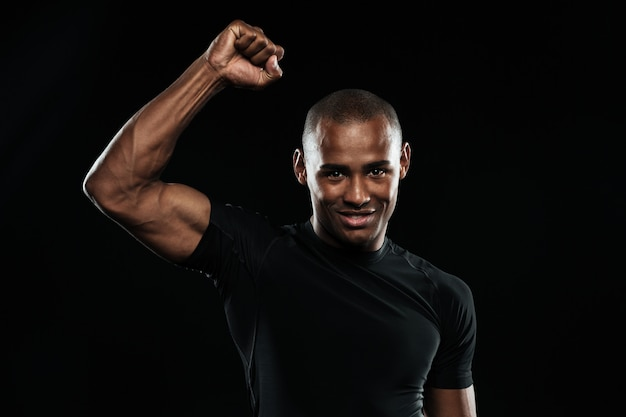 Jonge gelukkig afro-amerikaanse sport man viert zijn overwinning met opgeheven arm