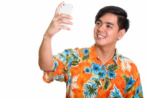 Jonge gelukkig aziatische man die lacht tijdens het nemen van selfie met mobiele ph