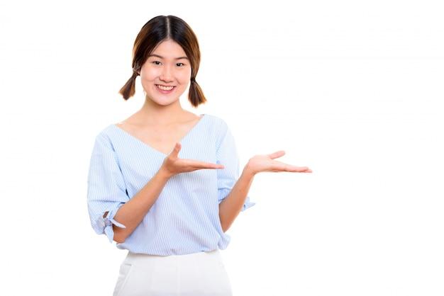 Jonge gelukkig aziatische vrouw die lacht terwijl iets wordt weergegeven