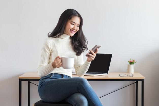Jonge gelukkig aziatische vrouw met behulp van een smartphone