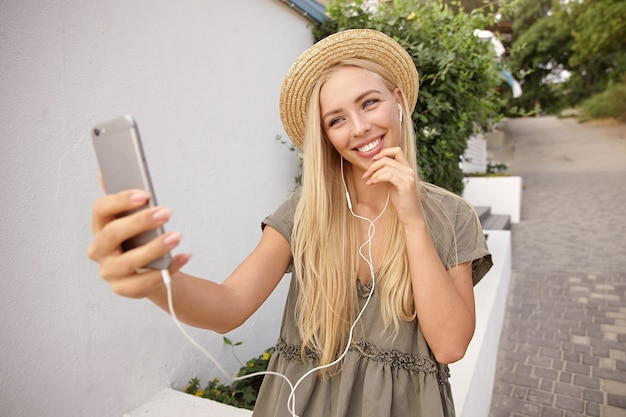 Jonge gelukkig blonde vrouw luisteren naar muziek tijdens het maken van selfie met haar mobiele telefoon, het dragen van casual linnen jurk en strooien hoed, vrolijk en tevreden kijken
