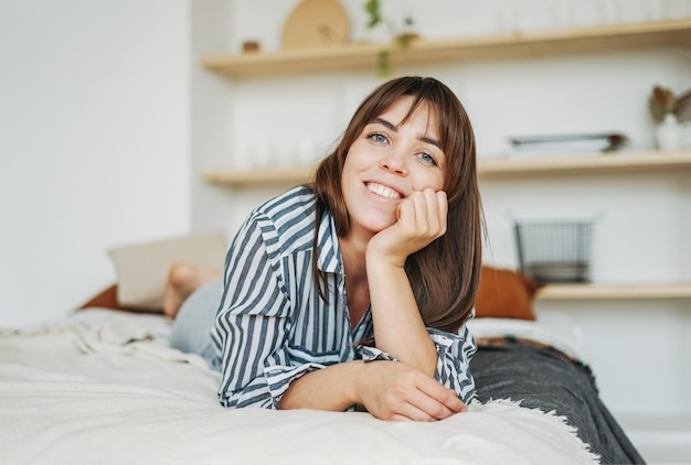 Jonge gelukkig brunette vrouw in vrijetijdskleding rusten op bed in het lichte interieur