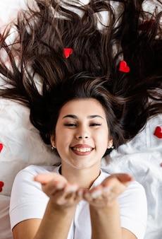 Jonge gelukkig brunette vrouw tot in het bed blaast een kus