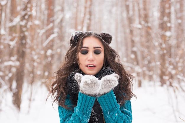 Jonge gelukkig brunette vrouw waait sneeuw in de natuur van de winter