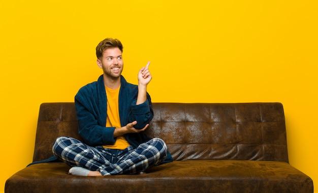 Jonge gelukkig dragen en pyjama's die glimlachen glimlachen, zijdelings, benieuwd zijnd, denkend een idee. zittend op een bank