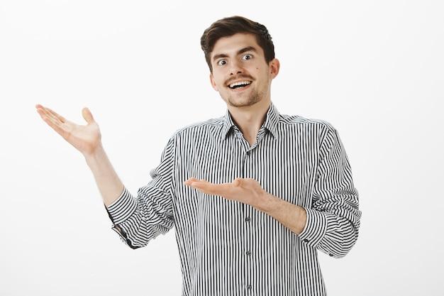 Jonge gelukkig europese man met baard en snor, naar links wijzend met handpalmen