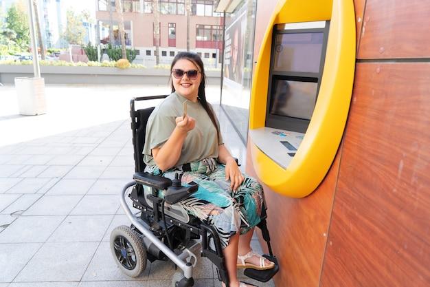 Jonge gelukkig gehandicapte vrouw in rolstoel met behulp van atm-geldautomaat en glimlachend in de camera op zonnige zomerdag