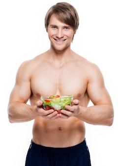 Jonge gelukkig gespierde man met een salade over witte muur.
