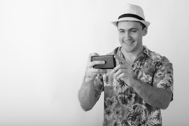 Jonge gelukkig gespierde toeristische man die lacht tijdens het nemen van foto met mobiele telefoon.