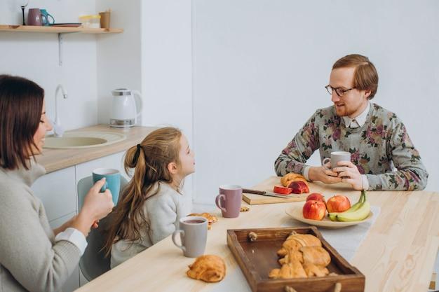 Jonge gelukkig gezin met twee kinderen samen ontbijten.