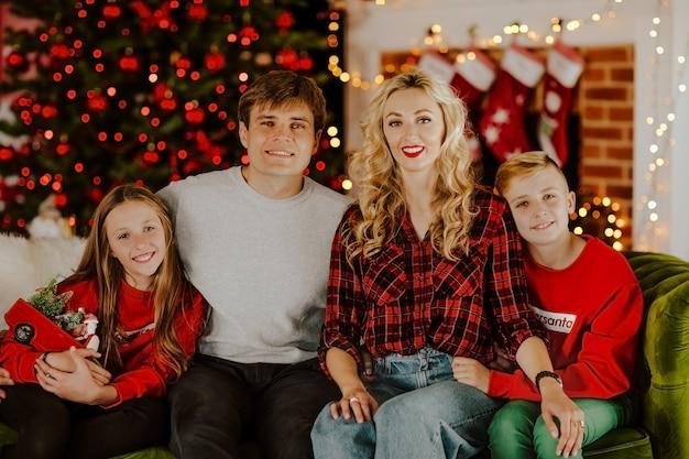 Jonge gelukkig gezin van vier in kerst kleding zitten en glimlachen in de woonkamer tegen kerstverlichting.