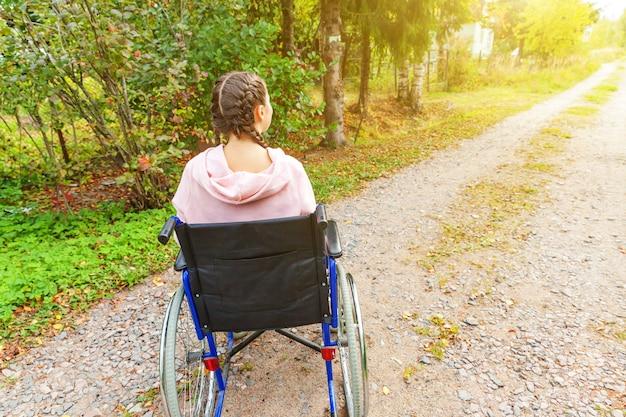 Jonge gelukkig handicap vrouw in rolstoel op weg buiten in de natuur