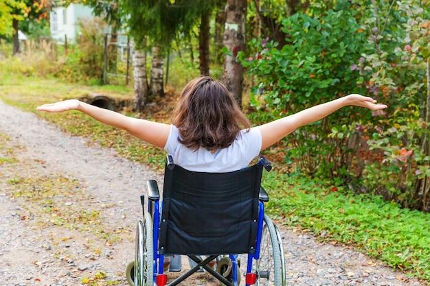 Jonge gelukkig handicap vrouw in rolstoel op weg in ziekenhuis park genieten van vrijheid