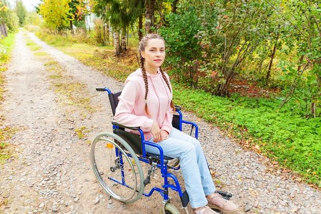Jonge gelukkig handicap vrouw in rolstoel op weg in ziekenhuis park