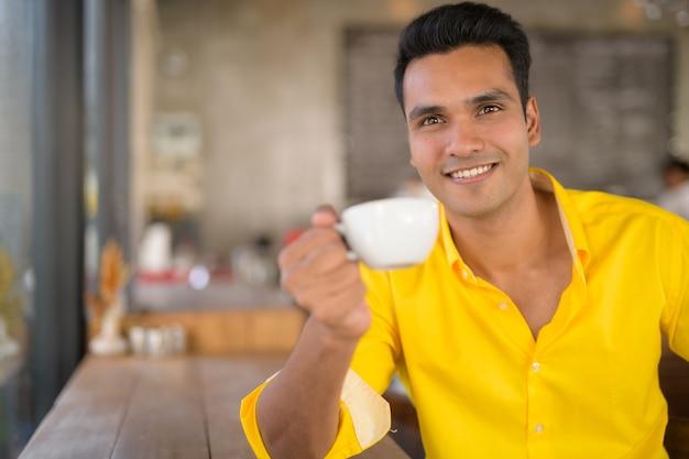 Jonge gelukkig indiase man koffie drinken bij het raam bij de coff