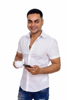 Jonge gelukkig indiase man met behulp van mobiele telefoon terwijl koffiekopje