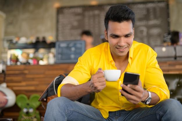 Jonge gelukkig indiase man met behulp van telefoon en zittend op de koffiesho