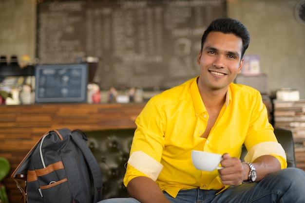 Jonge gelukkig indiase man zitten en koffie drinken bij de koffie